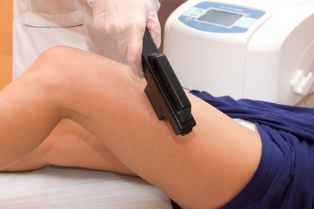 Laser epilation of leg in a modern beauty shop